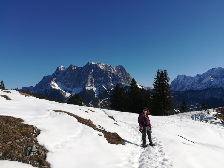 snowshoer on trail with Alps in the background