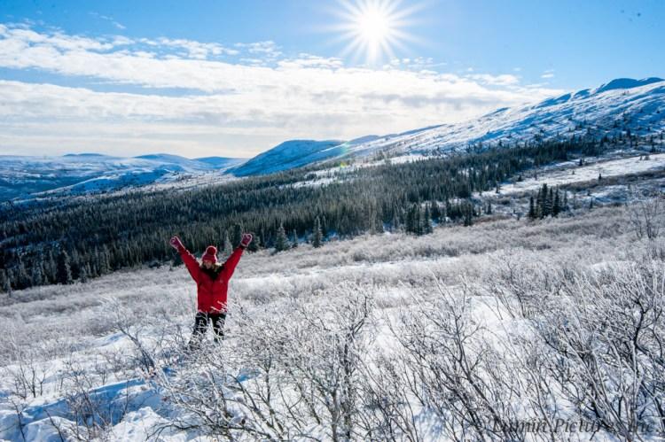 woman standing in Bonneville Ridge, Yukon under blue sky in winter