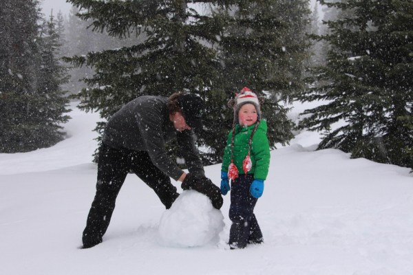 adult and child making a snowman in snow near Hilda Creek Hostel