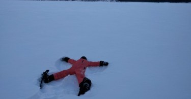 person lying with arms and legs spread out in the snow while wearing snowshoes