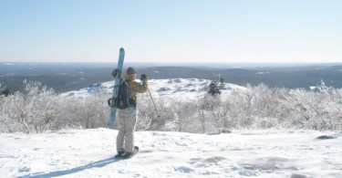 man looking out at view with snowboard in pack and on snowshoes