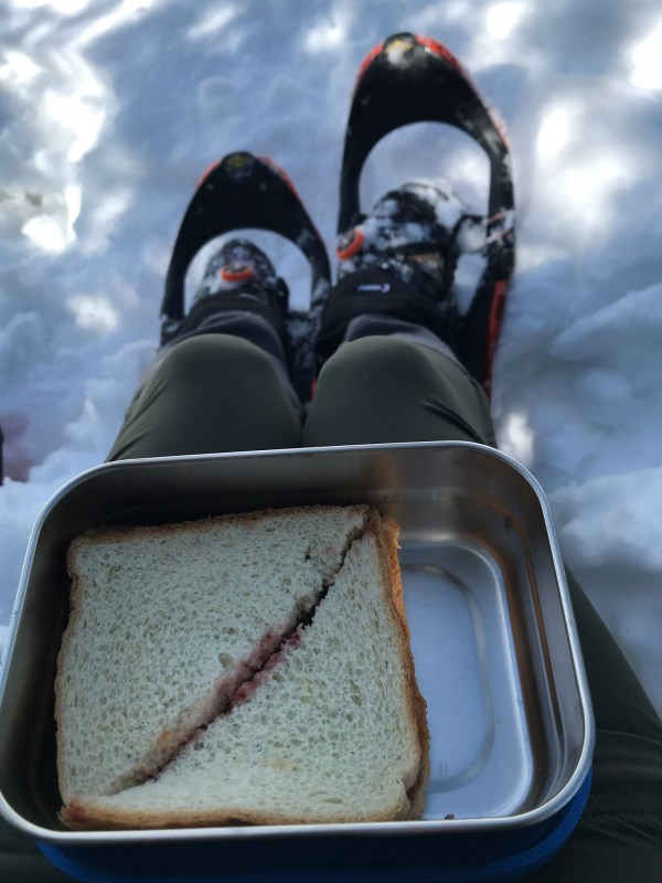 snack container with snowshoes and snow in background