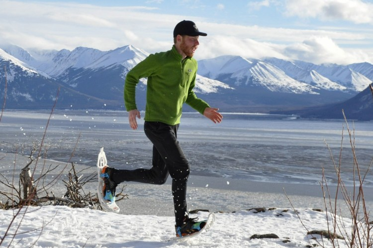 man running on snowshoes with mountains in background