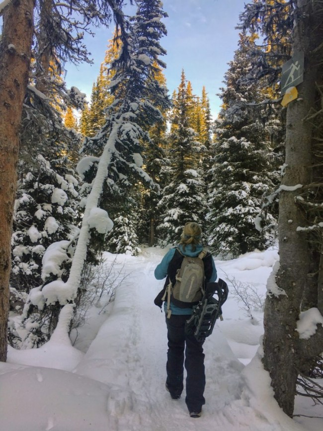 trail etiquette: person walking on trail with snow with snowshoes strapped to backpack