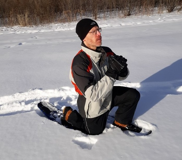 person demonstrating lunge on snowshoes in the snow