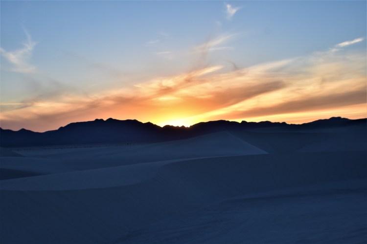 orange sunset behind White Sands National Park in NM