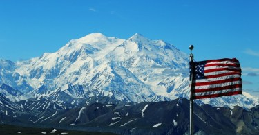 US flag with snowy mountain in background