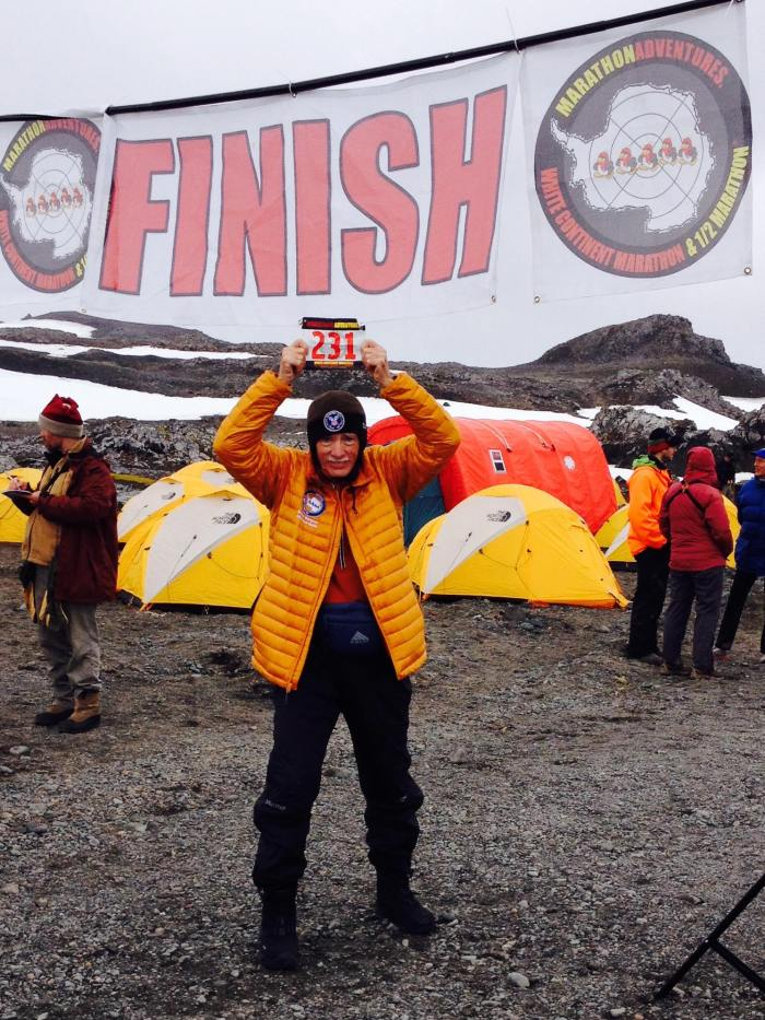 man holding up his racing number after his tenth completion of the continents