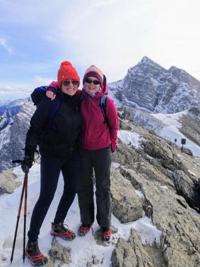 two women posing on top of Ha Ling Peak in microspikes