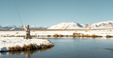 man fishing in winter with snow on ground
