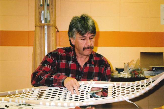man looking at Obijwe snowshoes on a table