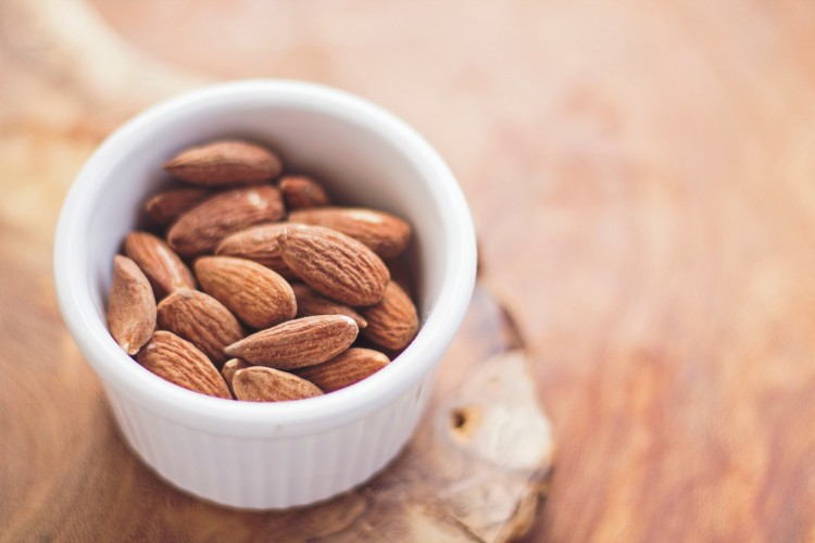 snowshoeing snacks: almonds in a small bowl on wood background