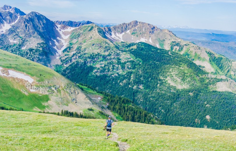 man running on trail with view of the mountains