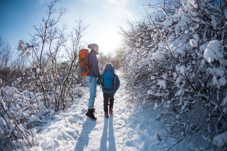 mom and child on winter hike in snow