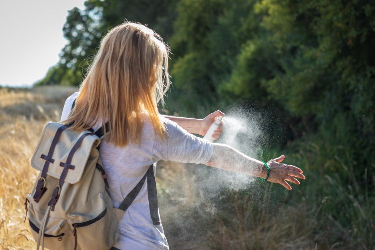 woman spraying mosquito repellant in outdoors