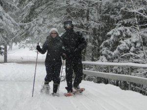 A snowshoeing couple enjoying fresh snowfall at Lapland Lake.