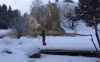 snowshoeing child in front of big, orange geyser mound