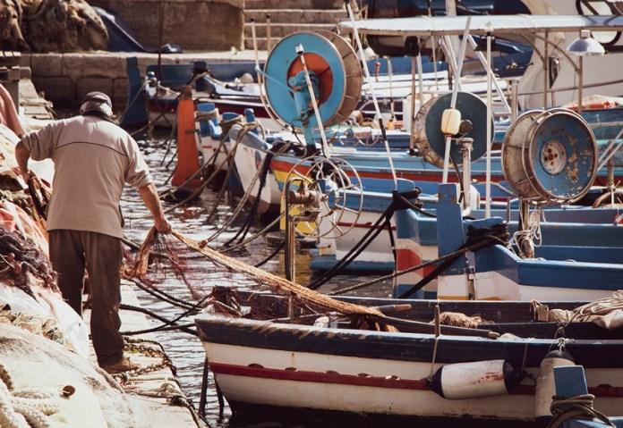 Un pescatore raccoglie le reti nel porto di Mondello a Palermo