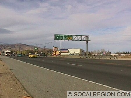Looking north at the northern junction of SR-58 (old US 466). This intersection has changed little since the days of the US highways. It was moved slightly to the north of the old intersection which existed right behind the overhead sign in the background. The sign reads : Bakersfield SR-58, Bishop-Reno SR-14.