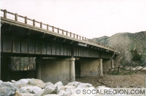 Underneath the bridge on the 1932 side.