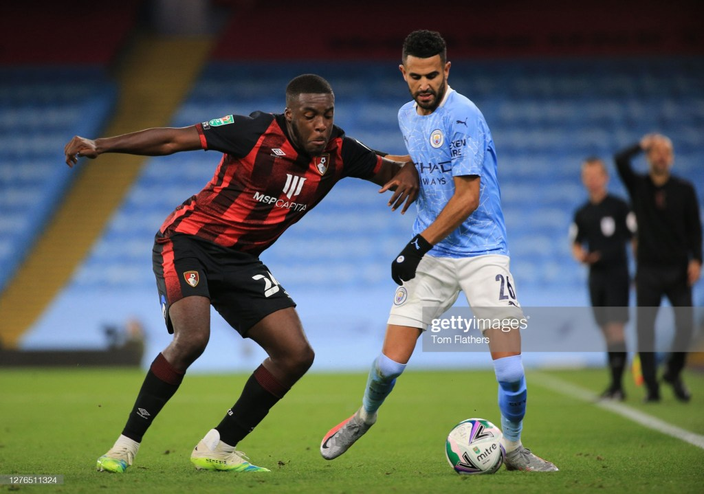 MANCHESTER, ENGLAND - SEPTEMBER 24: Nnamdi Ofoborh of AFC Bournemouth  battles for possession with  Riyad Mahrez of Manchester City   during the Carabao Cup third round match between Manchester City and AFC Bournemouth at Etihad Stadium on September 24, 2020 in Manchester, England. Football Stadiums around Europe remain empty due to the Coronavirus Pandemic as Government social distancing laws prohibit fans inside venues resulting in fixtures being played behind closed doors. (Photo by Tom Flathers/Manchester City FC via Getty Images)
