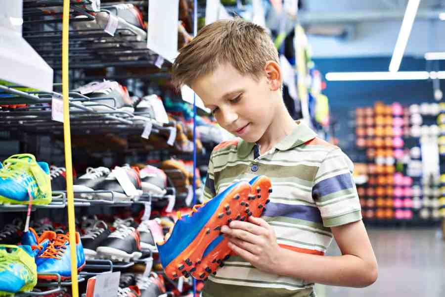 boy looking at soccer shoes in store
