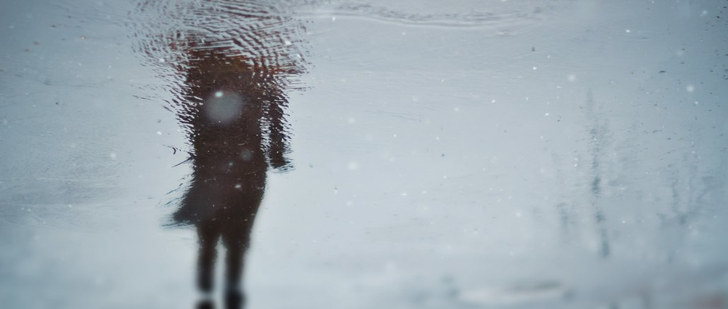 image of person reflected in puddle.