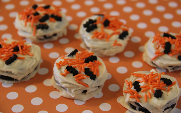 all you want to do is melt white chocolate chips and dip oreos right into it or you can spread it if thats any easier add some halloween sprinkles