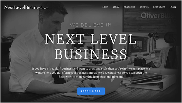 """This is a screenshot of the Next Level Business website, a business run by Oli Billson. In the upper left is the website name in white text, NextLevelBusiness.com. In the upper right are navigation options in white text. The options are Home, Story, Programs, Reviews Resources, and Login. In the center of the page, in white text, a heading says, """"We Believe in Next Level Business"""". Below the heading is a short statement, """"If you have a 'regular' business and want to grow and scale then you're in the right place. We want to help you transform your business into a Next Level Business so you can open the floodgates to more wealth, happiness and freedom."""" At the bottom of the page is a blue button with white text labeled """"Learn More"""". The web page background is a black and white photo of a white man with short hair sitting at a desk typing on an Apple laptop. He's wearing a white button-down shirt and a watch on his left wrist. On the desk is a book stacked on top of a white binder. He's sitting in an open office environment with other desks and computers."""