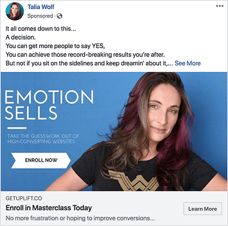 """This is a screenshot of a Facebook ad for a masterclass from Talia Wolf. In the ad text, each sentence is on a separate line. It says """"It all comes down to this . . . A decision. You can get more people to say YES. You can achieve those record-breaking results you're after. But not if you sit on the sidelines and keep dreamin' about it . . . """" After this text is a See More link. The ad image has a blue background with white text and a picture of Talia from the chest up. She is a white woman with brown and purple hair that falls below her shoulders. She's wearing a black t-shirt with a gold Wonder Woman logo. The text to the left of her photo says """"Emotion Sells"""" and """"Take the guesswork out of high-converting websites"""". Below this text is a white arrow with black text that says """"Enroll Now"""". Below the image is the following headline and text: """"Getuplift.co"""" and """"Enroll in Masterclass Today"""" and """"No more frustration or hoping to improve conversions"""". A Learn More button appears in the lower right."""