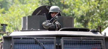 Kupwara: A security personnel takes position atop a military vehicle during search operations after an army commando was killed and another injured in a gunfight between hiding militants and security forces in a forested area of Jammu and Kashmir's Kupwara district, on July 11, 2018. (Photo: IANS)