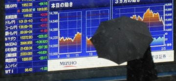 (140204) -- TOKYO, Feb. 4, 2014 (Xinhua) -- A man walks past an electronic board showing the stock index in Tokyo, Japan, Feb. 4, 2014. Tokyo stocks tumbled on Tuesday, with the Nikkei index ending 4.18 percent lower, hitting the lowest closing level since last October. The 225-issue Nikkei Stock Average dived 610.66 points, from Monday at 14,008.47, its lowest finish since Oct. 8. (Xinhua/Stringer) ****Authorized by ytfs****