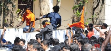 Palakkad: BJP workers jump a boundary wall during clashes with police during a protest amid a dawn-to-dusk Kerala shutdown called to denounce the visit of two women to the Sabarimala temple, that saw major violence, in Kerala's Palakkad on Jan 3, 2019. (Photo: IANS)