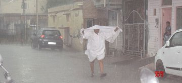 Mathura: A man tries to shield himself during heavy rain in Mathura, on April 17, 2019. (Photo: IANS)