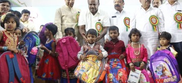 Bengaluru: Karnataka Chief Minister H. D. Kumaraswamy and Deputy Chief Minister G. Parameshwara distribute school bags among children at the inauguration of Karnataka Public School, in Bengaluru on June 14, 2019. (Photo: IANS)