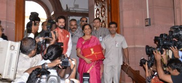 New Delhi: Union Finance Minister Nirmala Sitharaman along with Union Minister of State for Finance Anurag Thakur, arrives at Parliament to present the Union Budget 2019, in New Delhi on July 5, 2019. Setting a new precedent Union Finance Minister Nirmala Sitharaman on Friday is seen hugging the budget documents wrapped in a red cloth, the traditional 'bahi khaata' way, instead of the leather briefcase that until now her predecessors walked around with. (Photo: IANS)