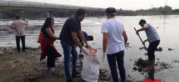 New Delhi: Newspaper hawkers clean the Yamuna river at Yamuna Chhath Ghat near ITO in Delhi. (Photo: IANS)