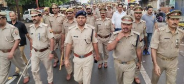 Banda (UP): Police personnel conduct flag march after tensions gripped Uttar Pradesh's Banda where meat shops said to be illegal were allegedly closed forcibly by some activists of Vishwa Hindu Parishad. (Photo: IANS)