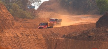 Navelim: A view of trucks moving amid mine fields near an iron plant at Navelim in Goa on March 13, 2018. BJP Goa MPs met the party's national president Amit Shah in the New Delhi on Tuesday and discussed the Supreme Court-imposed mining ban in Goa which is slated to come into effect from March 15. (Photo: IANS)