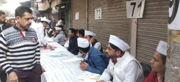 New Delhi: Supporters of Delhi Cabinet Minister and AAP's candidate from Ballimaran assembly seat, Imran Hussain seen volunteering in white jackets and caps, during voting for Delhi Assembly elections 2020, at Delhi's Ballimaran, on Feb 8, 2020. (Photo: IANS)
