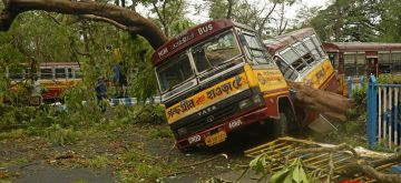 Kolkata: Uprooted trees leave vehicles damaged and roads blocked after Super Cyclone Amphan made its appearance on Wednesday, as it pummelled through the night over Kolkata and large parts of West Bengal leaving behind a trail of deaths as at least 12 people were killed; on May 21, 2020. (Photo: Kuntal Chakrabarty/IANS)