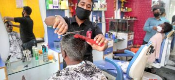 Bengaluru: A barber gives a haircut to a man at a salon in Bengaluru on the fourth day of the fourth phase of the nationwide lockdown imposed to mitigate the spread of coronavirus on May 21, 2020. (Photo: IANS)