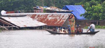 Morigaon: Villagers row their boat through floodwaters at Sildubi village following heavy rainfall that left Assam's Morigaon district inundated, on June 28, 2020. (Photo: IANS)