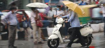 New Delhi: People shield themselves using umbrellas as rains lash New Delhi on Aug 13, 2020. (Photo: IANS)