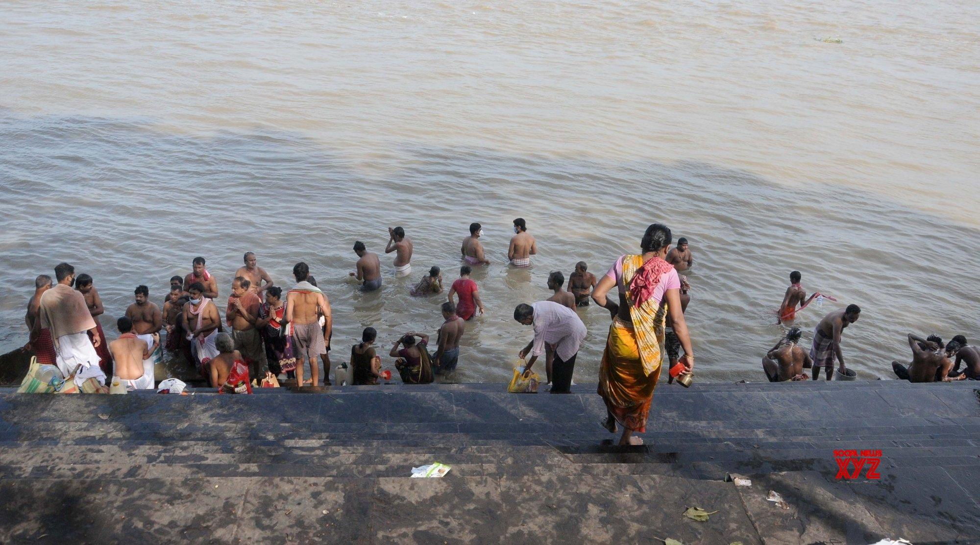 Kolkata: Devotees perform 'Tarpan' on the last day of 'Pitru Paksha' on the banks of Ganga river #Gallery