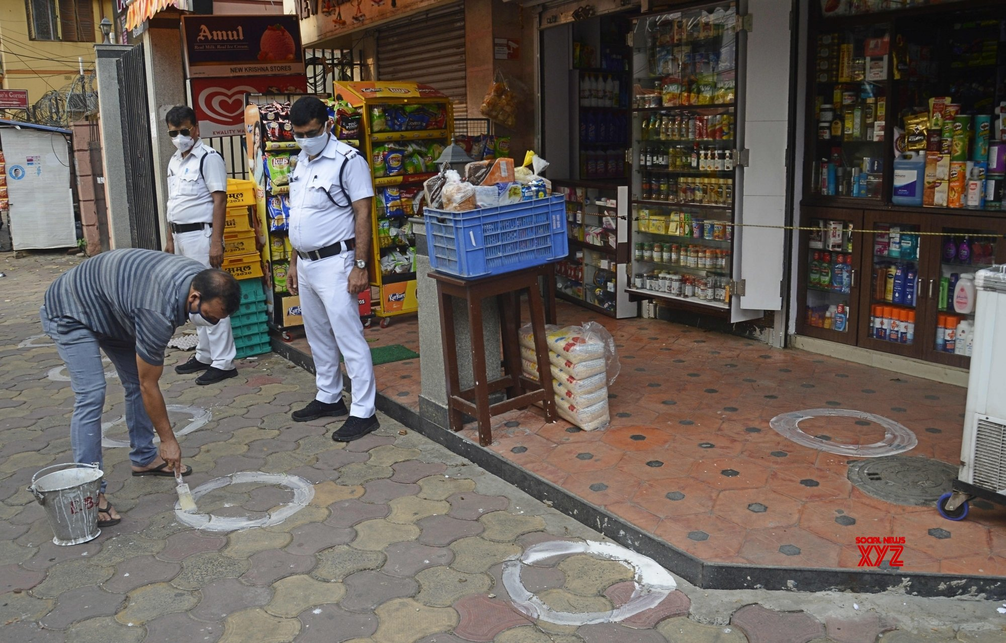Kolkata: Worker marking a circle for customers social distancing in front of shops during the coronavirus pandemic in Kolkata. #Gallery