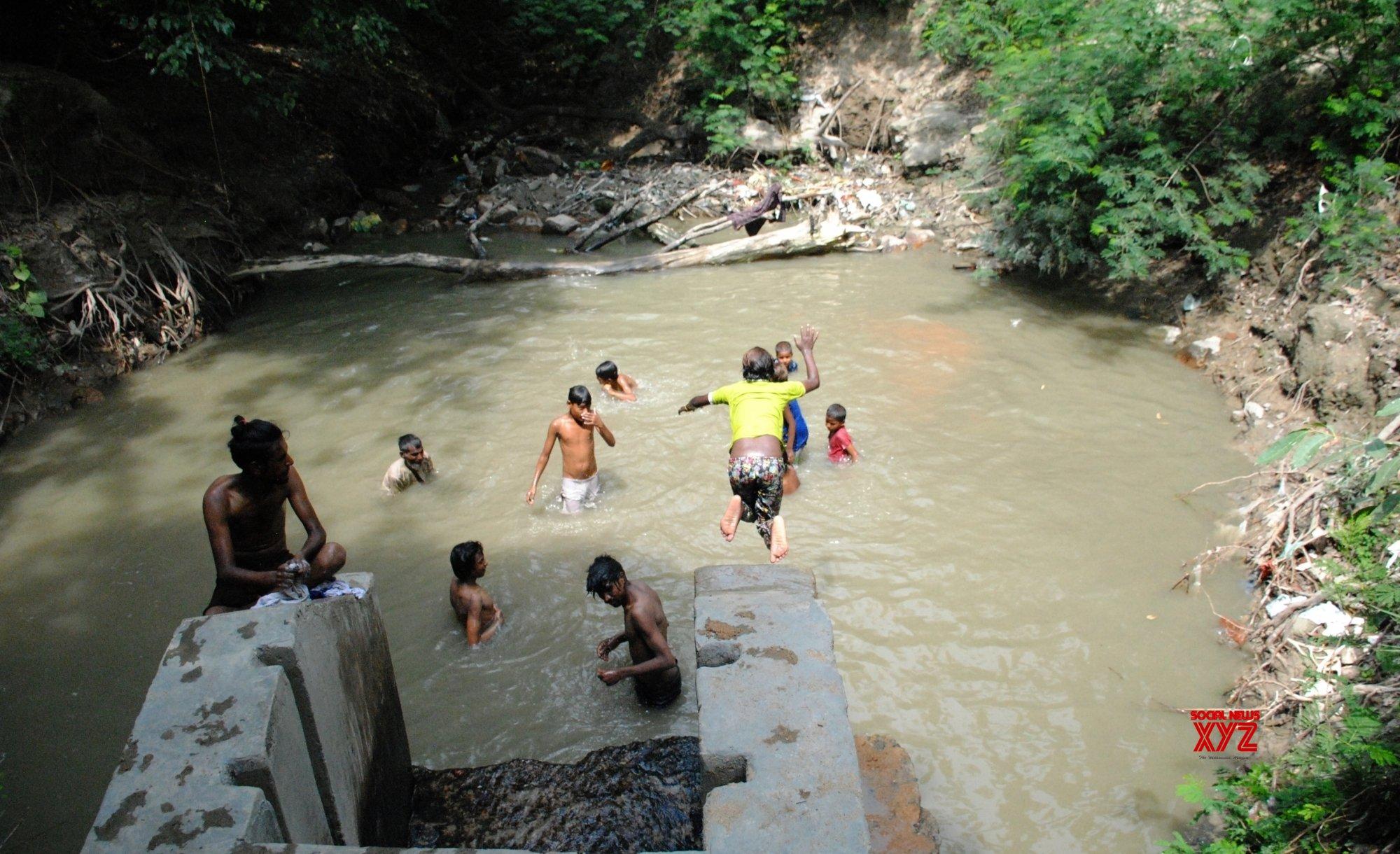 New Delhi: Children enjoying in water pond during hot weather in New Delhi. #Gallery