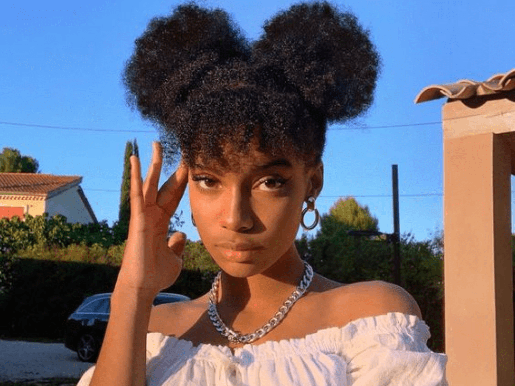 A black woman with beautiful curly hair shaped into buns and bangs