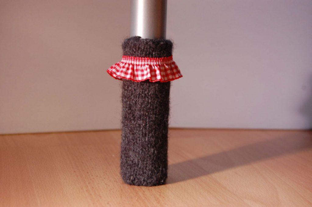 Stuhlbeinsocke mit Karo-Rüschenband stuhlbeinsocke Anleitung: Stuhlbein Socke stricken – mit Filzwolle