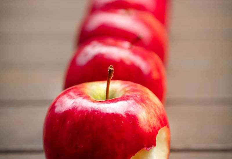 Reihe von Äpfeln mit dem vordersten angebissen